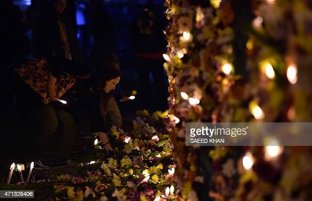 A woman places flowers at a floral sculpture that reads 'keep hope alive' during a candlelight vigil on Sydney Harbour foreshore on April 27 to call...