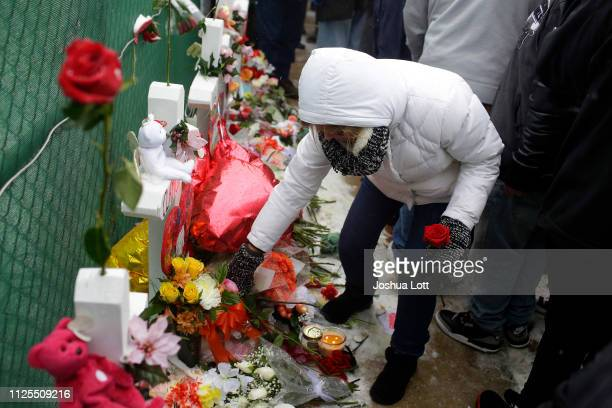 A woman places flowers at a makeshift memorial outside Henry Pratt Company on February 17 2019 in Aurora Illinois Six people including a gunman were...