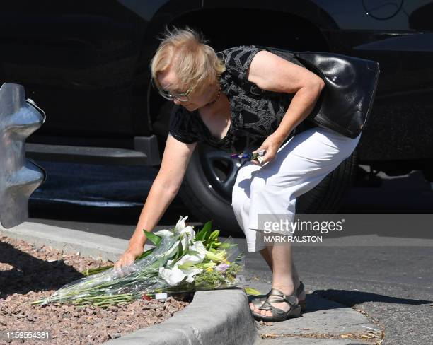 A woman places flowers at a makeshift memorial outside the Cielo Vista Mall WalMart where a shooting left 20 people dead in El Paso Texas on August 4...