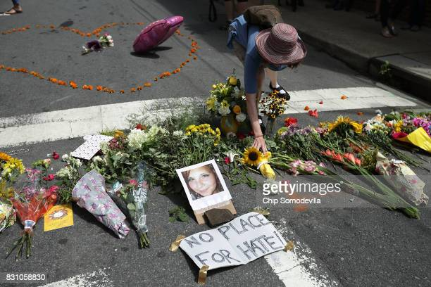 A woman places flowers at an informal memorial to 32yearold Heather Heyer who was killed when a car plowed into a crowd of people protesting against...