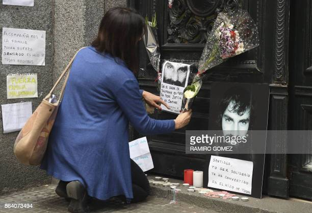 A woman places flowers at the door step of the judicial morgue where an autopsy of the corpse of Santiago Maldonado disappeared on August 1st during...