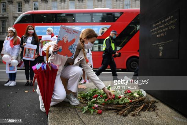 Woman places flowers at the Women of World War II statue on Whitehall, in central London on October 10 during a march in solidarity with the women of...