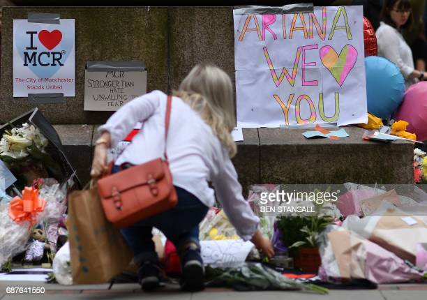 TOPSHOT A woman places flowers beneath a sign that reads 'Ariana we love you' in St Ann's Square in Manchester northwest England on May 24 in tribute...
