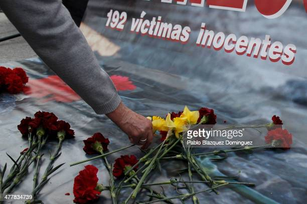 A woman places flowers for the victims of Madrid train bombings during a memorial gathering outside Atocha railway station on the 10th anniversary on...
