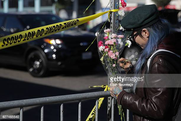 A woman places flowers on a post outside a police line following an overnight fire that claimed the lives of at least nine people at a warehouse in...