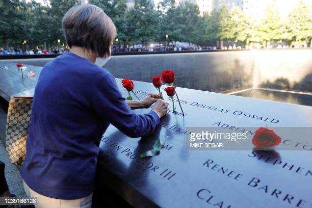 Woman places flowers on the 9/11 Memorial on the 20th anniversary of the September 11 attacks in Manhattan, New York on September 11, 2021.