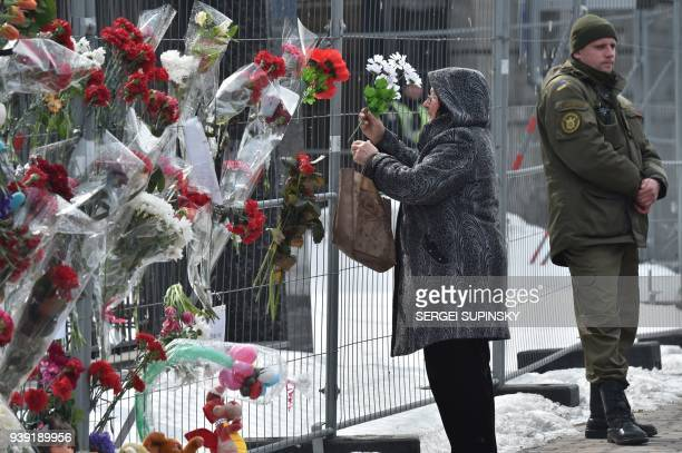 A woman places flowers on the fence outside the Russian Embassy in Kiev on March 28 in tribute to the victims of a shopping mall fire in the Siberian...