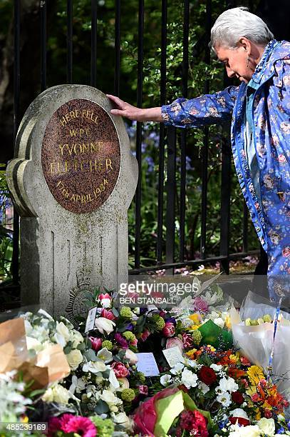 A woman places her hand on the memorial stone after laying a wreath at the spot where British police officer Yvonne Fletcher was killed during a...