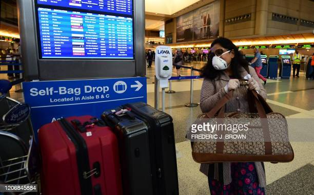 Woman places her luggage on a cart beside a flight onformation screen at Los Angeles International Airport on March 12, 2020 one day before a US...