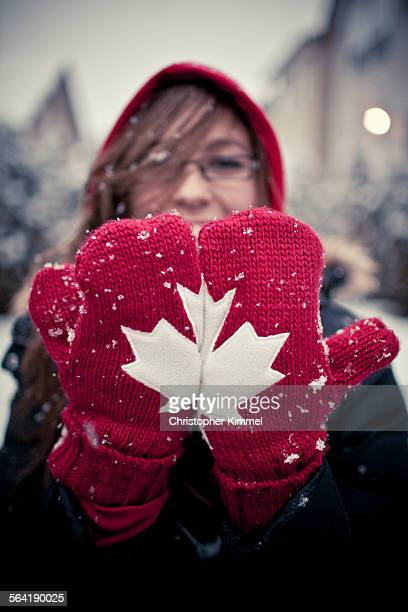A woman places her mittens side by sde to create a Maple Leaf.