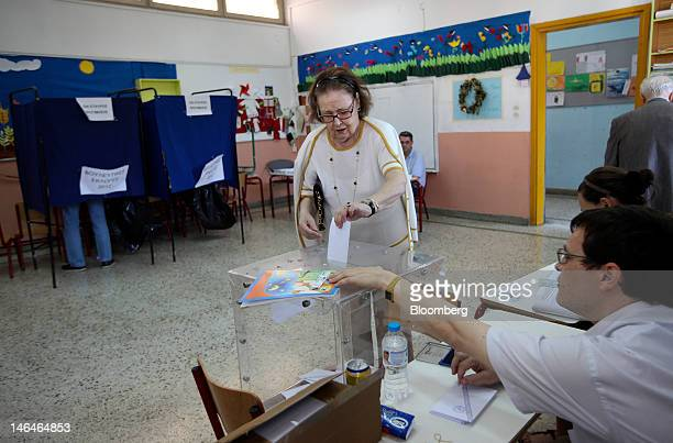 A woman places her sealed and stamped ballot paper into a box as she casts her vote in the second round of the Greek general elections at a polling...