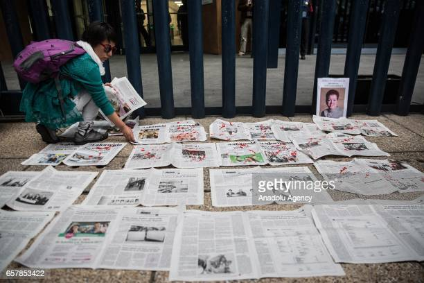 A woman places newspaper pages with fake blood during a protest against the recent murder of the correspondent journalist Miroslava Breach of 'La...