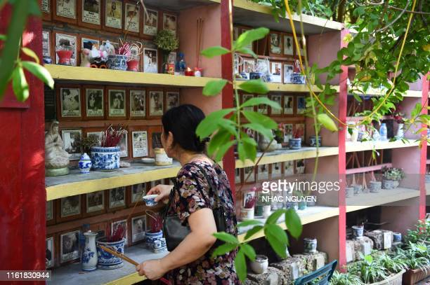 A woman places offerings to her pet at Te Dong Vat Nga pagoda which means all lives are equal a cemetary for dogs and cats in Hanoi on August 15 2019...
