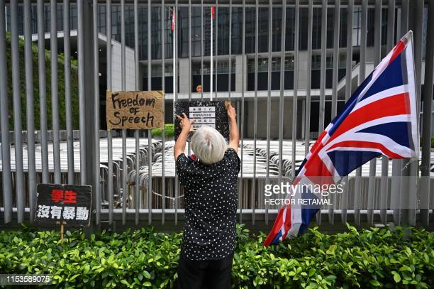 A woman places signs on a fence next to the Legislative Council building in Hong Kong on July 4 2019 Hong Kong authorities on July 3 vowed to hunt...