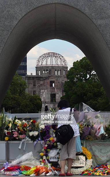 A woman placesc flowers at the monument for atomic bomb vicitims at the Hiroshima Peace Memorial Park on August 5 2012 in Hiroshima Japan Tomorrow...