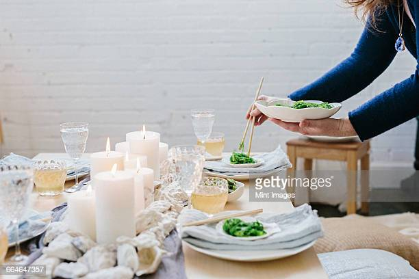A woman placing a plate of food on a table decorated with lighted candles.