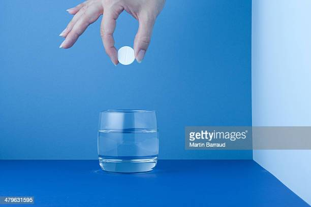 Woman placing a tablet in a glass of water