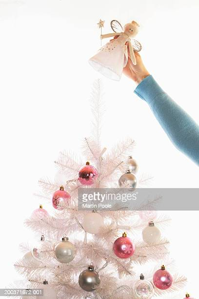 Woman placing angel on top of fake white Christmas tree, high section