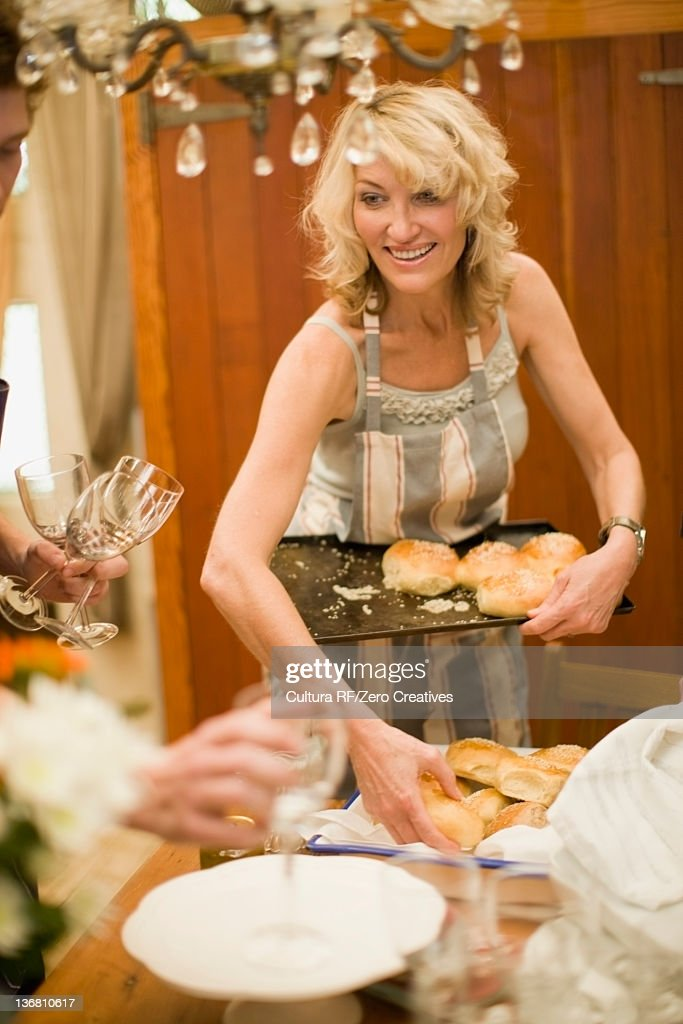 Woman placing bread rolls on tray : Stock Photo