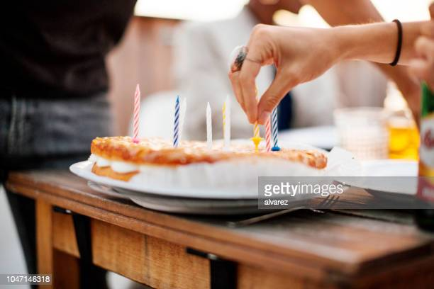 woman placing candles on a cake - positioning stock pictures, royalty-free photos & images