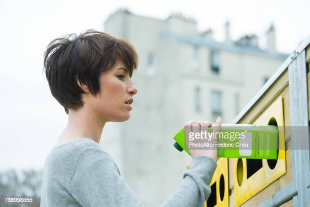 woman placing carton in recycling bin - recycling bin stock pictures, royalty-free photos & images