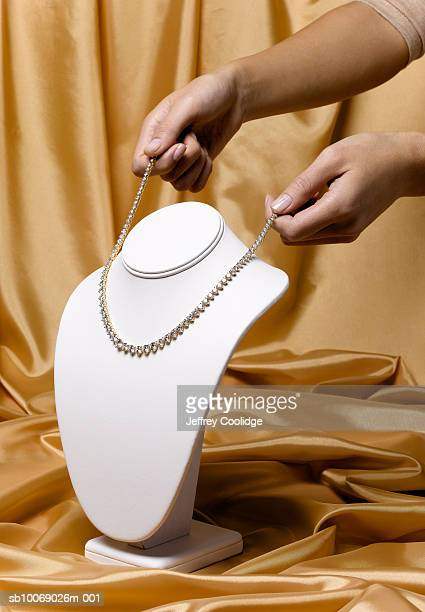woman placing diamond necklace on jewelry stand, studio shot - choker stock pictures, royalty-free photos & images