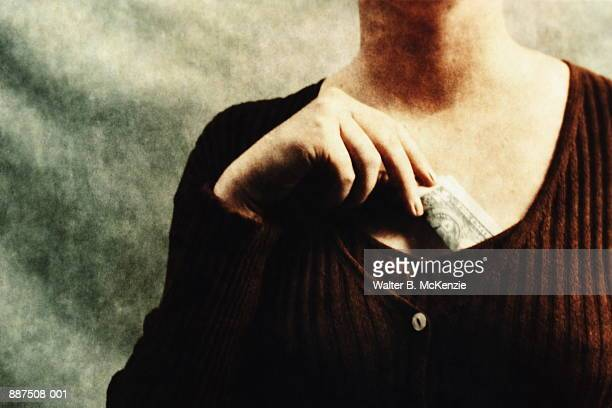 Woman placing dollar in blouse (paper negative)