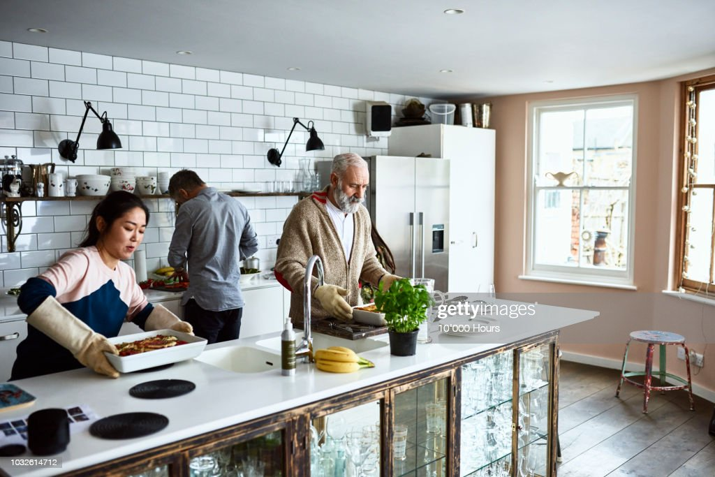 Woman placing hot lasagne dish on counter with father in law in kitchen : Stock Photo