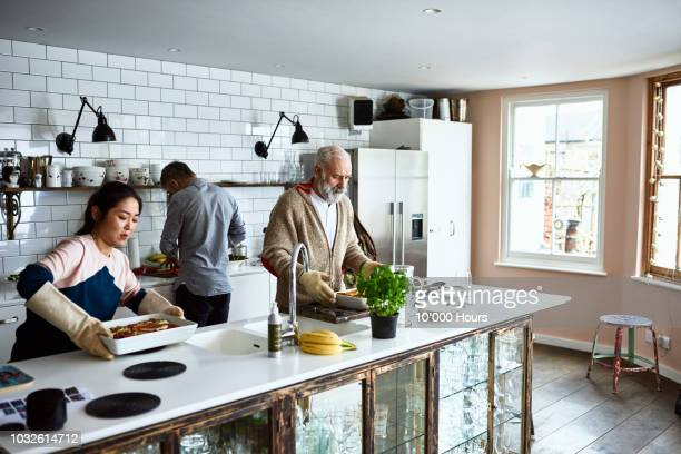 Woman placing hot lasagne dish on counter with father in law in kitchen