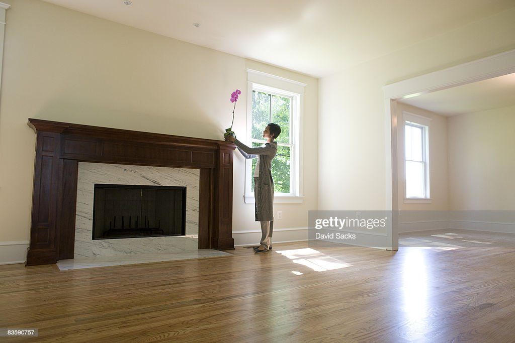Woman placing orchid on fireplace in empty room : Stock Photo