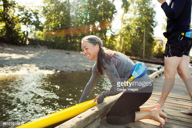 woman placing paddleboard on river while man standing beside at pier - older woman bending over stock pictures, royalty-free photos & images