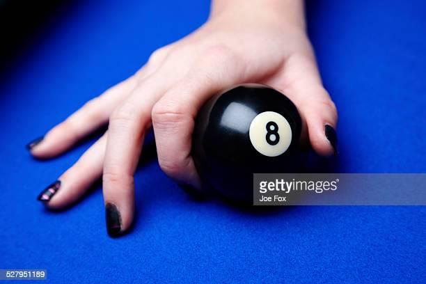 Woman placing pool 8 ball on table