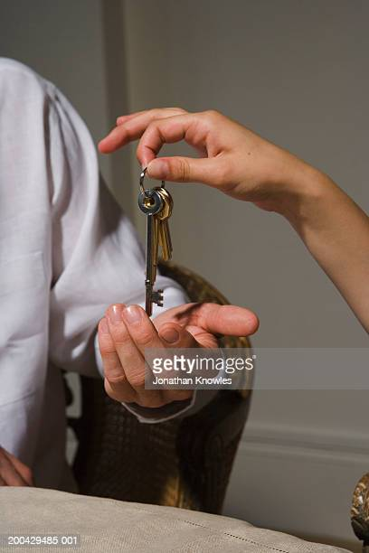 Woman placing set of house keys into man's hand, close-up