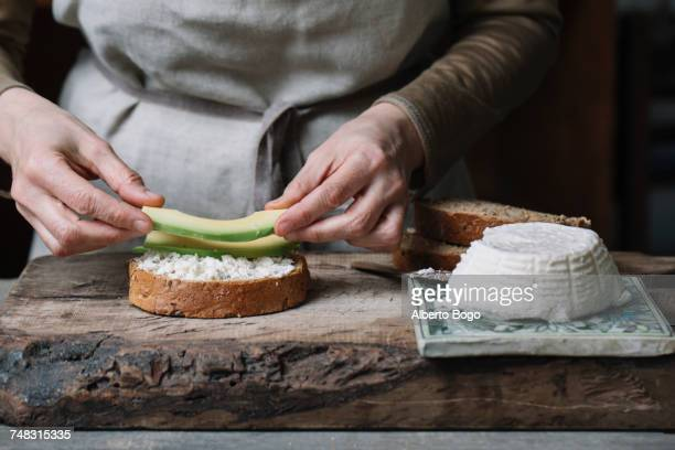 Woman placing slices of avocado onto sliced bread with ricotta, mid section