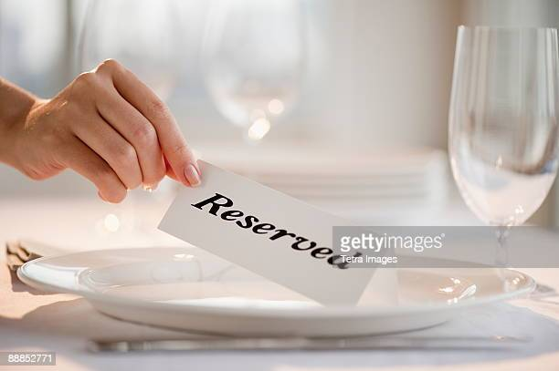 Woman placing tag on restaurant table, close-up