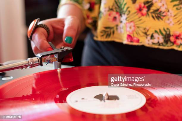 woman placing the needle of a record player on a vinyl - recording studio stock pictures, royalty-free photos & images