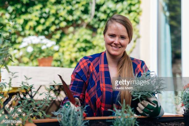 Woman planting on her garden deck.