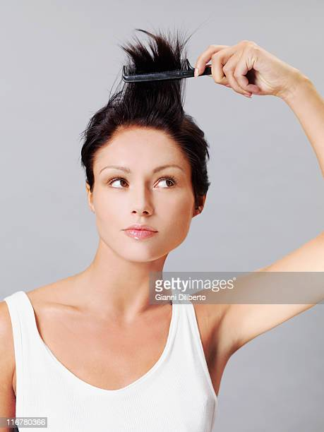 A woman playfully combing her hair