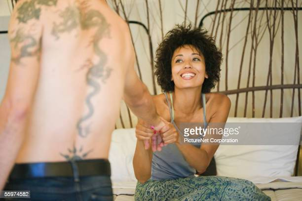 Woman playfully pulling man towards bed