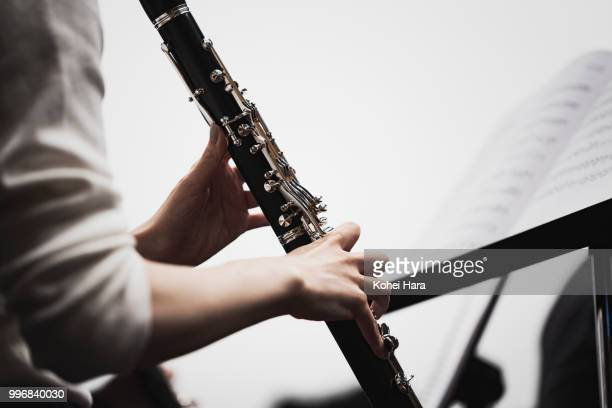 woman playing a clarinet at concert hall in rehearsal - clarinete fotografías e imágenes de stock