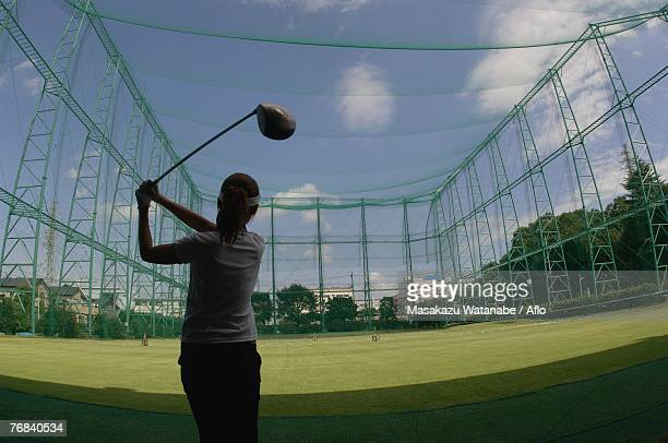 Woman playing a golf stroke at a golf range