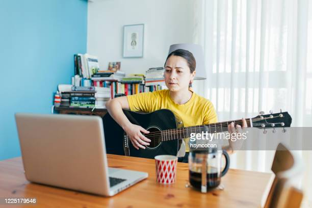 woman playing a guitar at home - country and western stock pictures, royalty-free photos & images