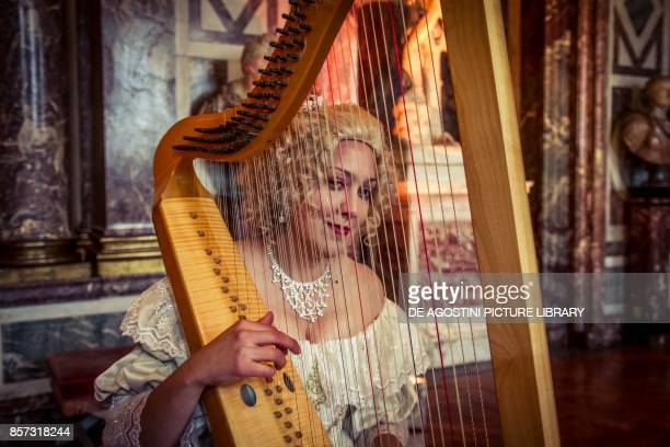 Woman playing a harp courtship party with participants wearing clothes from the Louis XIV period Palace of Versailles France Historical reenactment