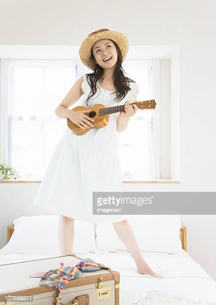 A woman playing a ukulele