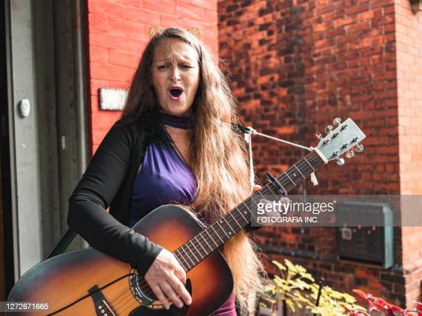 woman playing acoustic guitar - hamiltonmusical stock pictures, royalty-free photos & images
