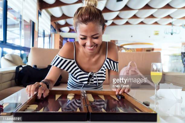 woman playing backgammon in hotel lobby - backgammon stock pictures, royalty-free photos & images