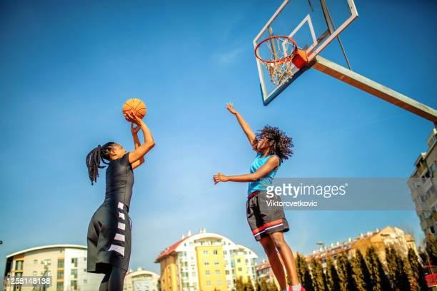 woman playing basketball on the playground - atirar ao cesto imagens e fotografias de stock