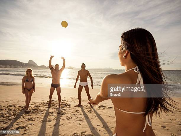 Woman playing beach volleyball with her friends during summer day.