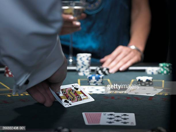 Woman playing Blackjack, croupier turning over knave, close-up