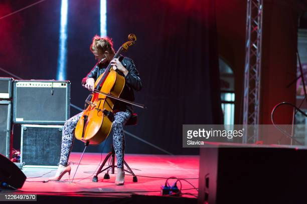 woman playing cello on the stage - classical concert stock pictures, royalty-free photos & images